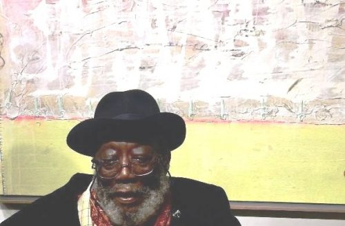 Frank bowling infront of painting